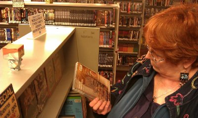 Peg reading the details on the jacket of a DVD at Stadium Video in Tacoma. Note the Marty Campbell doll on the top shelf - photo.