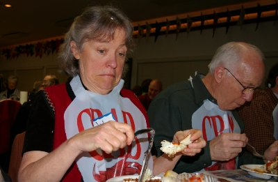 Jan Runbeck eating crab at the Totem Yacht Club fundraiser - photo.
