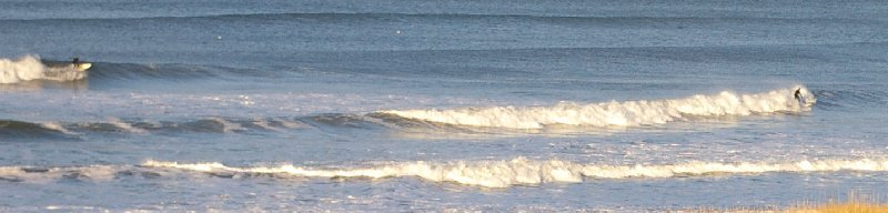 Two wetsuited surfers in the icy waters in December at Ocean Shores.