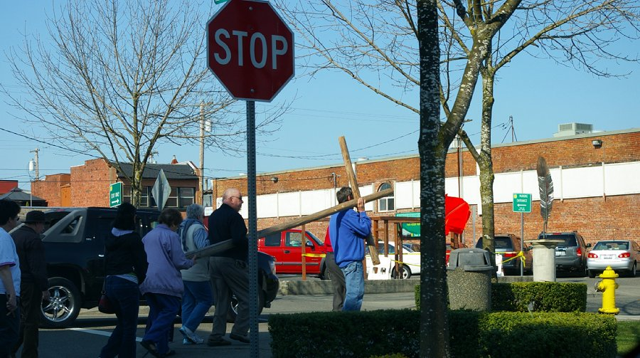 The Christian faithful walking on the sidewalk and carrying a cross in downtown Puyallup, Washington.