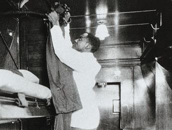 A Pullman porter making up a bed.