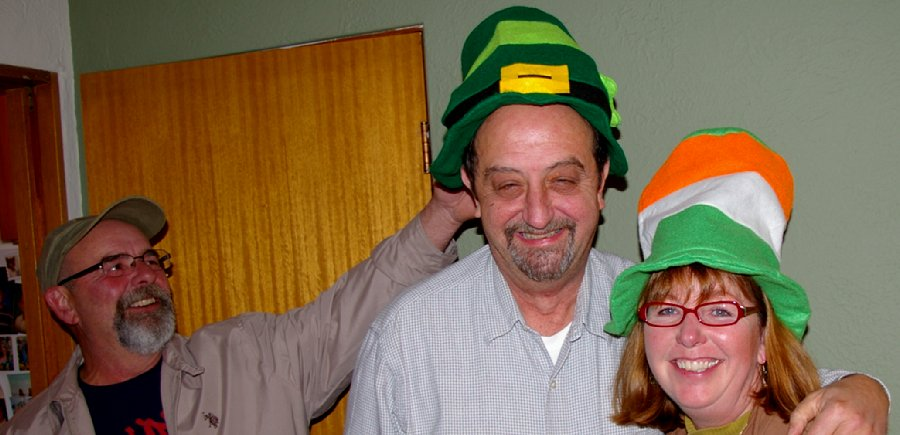 Randy headslaps Donn and Donn and Debbie wear St. Patrick's Day Party hats supplied by Jan Runbeck - photo.
