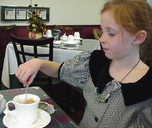 Demetria regally stirs her tea.